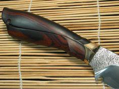 """Stahl: 1.1545 Länge: 30 cm Länge der Schneide: 15 cm Dicke: 4,5 – 1 mm Parier-Element: Bronze Griff: Wüsteneisenholz Härte: 59 HRC Besonderheiten: Differentiell mit """"Hamon"""" gehärtet, Erl vernietet, Griff geschnitzt und Scheide strukturiert. Status: Schon verkauft. Neugierig, wie dieses Messer entstanden ist? Bitteschön:"""