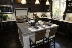 The white island with dark grey counter contrasts nicely with the dark cabinets of this kitchen.