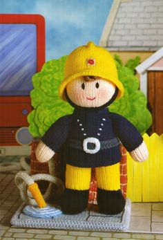 "From Jean Greenhowe's 'Mascot Dolls' collection comes this rather cute Fireman. Like all the mascot dolls he comes with his own appropriate little display stand. The stand is not designed as a toy, but he is so he can be removed to go and rescue all those cats stuck up trees! He is knitted with DK wool, is easy to make and the doll is 23cm/9"" tall (excl. hat). Designed and published by Jean Greenhowe Designs in 1993."