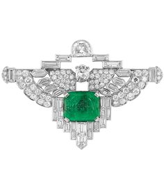 An Art Deco Egyptian Revival Platinum, Diamond and Carved Emerald Brooch, Circa 1930. Of geometric design, centring one cushion-shaped carved emerald approximately 11.8 x 14.2 x 6.0 mm., topped by one half moon-shaped diamond, accented by one oval briolette diamond, flanked by stylised wings, set with 32 baguette and bullet-shaped and 70 old European and single-cut diamonds. #ArtDeco #EgyptianRevival #brooch