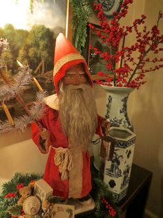 """A German Santa """" nodder. He holds his original feather tree with candle holders in his right hand and a tin and glass candle lantern in his left. Toys sit in a basket at his feet Saint Nick, Saint Nicholas, Candle Lanterns, Glass Candle, Father Christmas, Christmas Carol, My Teddy Bear, Feather Tree, Candy Containers"""