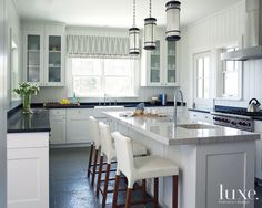 Island Living: Perfect Getaway For a Manhattan Family --- THE KITCHEN - Knicker counterstools by Blu Dot pull up to a classic white quartzite countertop by ABC Stone, while peripheral counters are showcased in absolute black granite by North Shore Stone and Mason Supply Corp. Charles Edwards' Round Manhattan lanterns provide task lighting above.