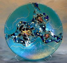 Three sea turtles decorated with dichroic glass in many layers and mosaic-like chips of colorful iridized and dichroic glass flow through this fused and slumped glass platter with gold pen work.