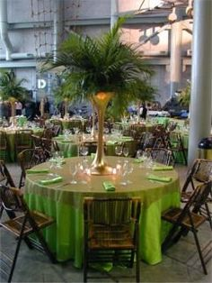 These palm leaf centerpieces in tall gold vases are so cool!!!