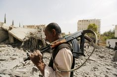 Week of Jun 13-19, 2015 A guard on Monday walks past a home destroyed by Saudi-led airstrikes in San'a, Yemen. KHALED ABDULLAH/REUTERS