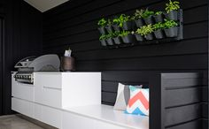 Wall planter and black weatherboard create a sophisticated backdrop for the covered BBQ area. Backdrops, House Design, House, Show Home, Wall Planter, Home, Blocks, Wall, Outdoor Living