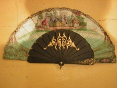 Circa early 19th century. Hand fan from Spain. Wood and paper. Black lacquer painted frame with gold scroll-type painting and a center of roses. Spanish dancers and musicians painted on paper front of fan and a smaller group of figures on back. The front side of closed fan has a small metal mirror Scroll work and roses on back. At Chatham Historical Society. #chathamhistoricalsociety, #fan, #19thcentury, #atwoodhouse, #antiquefan, #chatham, #capecod