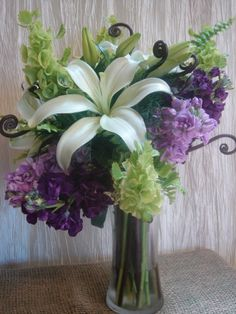 white Asiatic lily, fiddlehead fern, bells of Ireland, purple & lavender stock, Boston fern