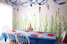 "Under the sea theme with seaweed wall and ""waves"" above. Darling ideas (shark teeth, squid cake, grapes on a stick...)"