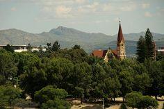 Vista geral das montanhas de Windhoek e da Christus Kirche, um dos principais símbolos arquitetônicos da capital da Namíbia. A inauguração desse templo religioso, no alto de uma pequena colina, marcou a paz estabelecida entre os colonizadores alemães e os povos nativos