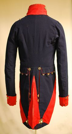 This dark blue wool coat has scarlet facings, collar, cuffs and turnbacks, and is in the style worn by infantry officers of the New York State Militia during the War of 1812. (Parks Canada)