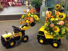 Toy tonka equipment with fresh arrangements designed by Le Jardin in Edinboro , Pa.