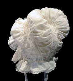 "Mob Cap: ca. 1830, English, muslin. ""White striped and spotted muslin mop cap with four pouches for curls. Decorated with strips of embroidery."""