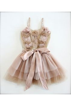 Neutral colored tutu dress with accents of blush pink. Soft, cotton bodice is adorned with tulle rosettes and beaded silk flowers. Tiered tutu skirt and silk bow ties at waist.