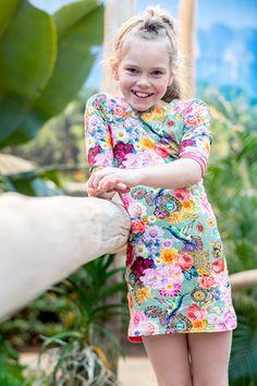 Mu-Chica Jurkje Floral!Mu-Chica tricot jurkje in all-over digitale print bloemen, vogels, vlinders.  Jurkje met mouwen tot boven aan de ellebogen. Mouwen afgezet met koraal roze boorden.  Achterkant jurkje koraal roze.  Jurkje loopt aan de onderkant rond af en heeft aan beide kanten een splitje.  Materiaal: 95% katoen 5% elastaan