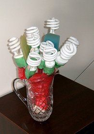 Housewarming Bouquet ~ Every stem in the crystal vase is a kitchen utensil attached to a compact fluorescent bulb with green painter's tape (spatula, salad spoon, serving spoon, etc). Taken apart, the entire gift is useful and practical