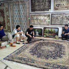 The boy is taking video of handmade silk rug in our showroom. www.yilongcarpet.com