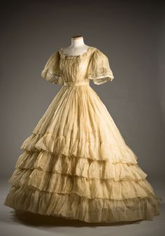 Starched organdy dress, 1865. Typical of mid-19th century styling, the very full skirt was worn over a hoop petticoat and is further widened by layers of ruffles. The starch used on this garment has...