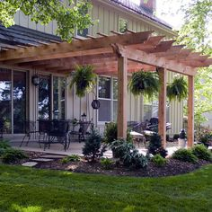 Attached to the house, this wood pergola shades the patio and provides an overhead structure for hanging plants.