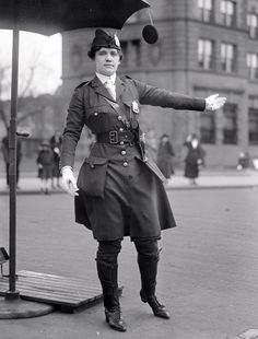 Leola King, America's first female traffic cop (1918) >>>> Mrs. L.O. King, a traffic control police officer. Standing beneath an umbrella for shade, directing traffic. Notice that her umbrella has a small mirror so she can see behind her., 1918. Photo by Harris & Ewing.