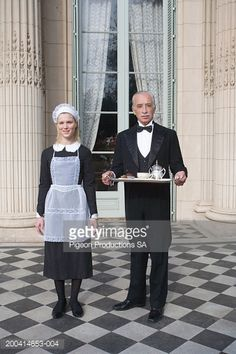 Stock Photo : Butler with maid holding tray, portrait