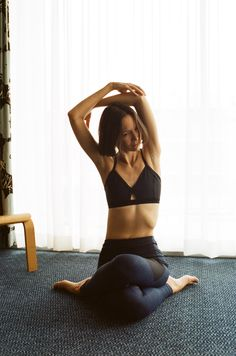 It's important to stretch. Pretty model wearing the Steeplechase Sports Bra and the Warmup Leggings from Outdoor Voices.