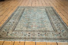 Stunning rug with floral design atop a slate blue field. Secondary colors include blush rose, ivory and beige.