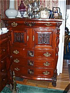 This Victorian High Boy is very typical of the period: Late 19th century -- Woods used: mahogany, walnut, rosewood -- Description: heavy, massive, substantial; dark finish; clumsy design; ornate carvings and decorations; marble tops used. (No marble top here, but other images of Victorian furniture on this board demonstrate the use of marble tops.