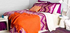 College rooms are always about bold patterns (duvet cover), bright colors and fun textures (mohair throw in mango!) and BASIC SHEETS (nice cream sheets). Even though this photo is not my personal style, it does a pretty good job of summing up a fun bed.