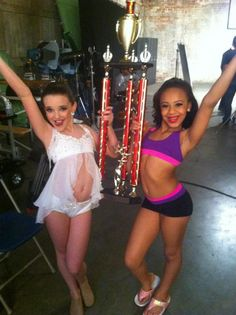 Dance Moms Kendall and Nia posing with a trophy.