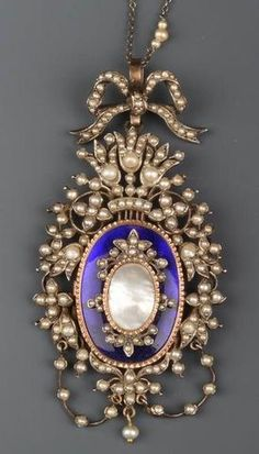 Pendentif porte photo en argent - il présente un médaillon central à fond d'émail entourant une perle nacrée, l'entourage ajouré, serti de perles d'eau douce, surmonté d'un noeud de ruban avec chainette. Fin du XIXème siècle.