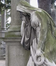 The depths of sorrow.In sadness, silence and solitude;  mourning women,   cemetary of Mechelen, Belgium