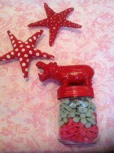 Porta nastri e passamanerie o attache, realizzato con barattolo di nutella vuoto, ippopotamo di plastica e smalto rosso.