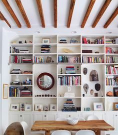 "strategically remove bookcase shelves to create larger ""cubbies"" within the shelving unit - breaks up the monotony of horizontal parallel lines, allows for larger decorative pieces to be incorporated, and creates the illusion of height by drawing the eyes upward (in my opinion, at least)"