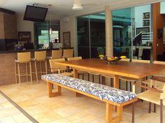 Balcão com resvestimento imitando madeira e tampo granito preto. TV sobre balcão. Mesa e bancos em madeira e banquetas em fibra (sintética?)