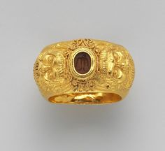 Gold ring with embossed satyr masks on carnelian intaglio, bird, Etruscan, Late Archaic, early 5th century BC. | From a tomb group allegedly from Vulci, one of the richest and most impressive sets of Etruscan jewelry ever found. | The Met