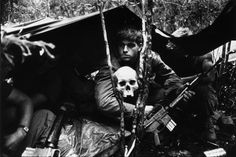 A human skull keeps watch over US soldiers encamped in the Vietnamese jungle by Terry Fincher, October 1968
