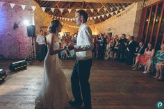 This wedding photo features the bride and groom performing their first dance in a mediaeval barn in Kingston, Dorset. Documentary wedding photography by Dorset wedding photographer.