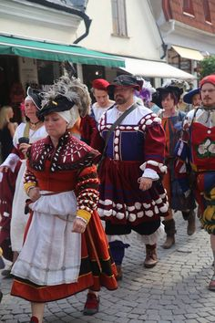 Landsknecht on parade. Both men's and women's garb. Love the waffenrock and her gollar