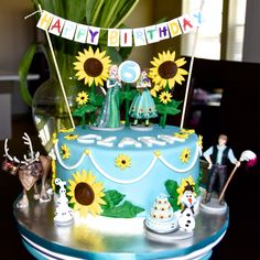 Frozen fever cake with Disney Figurines, sunflowers and banner.