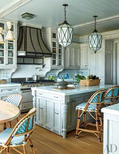 The kitchen is appointed with a RangeCraft hood, a Lacanche range, Waterworks sink fittings, and cabinet hardware by Sun Valley Bronze; the vintage lanterns are from Olde Good Things, and the chairs are by TK Collections