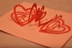 Il découpe une spirale dans un carton rouge pour faire la plus géniale des cartes POP-UP pour la Saint-Valentin :)