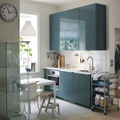 A small, modern kitchen with white walls and high-gloss grey-turquoise doors.