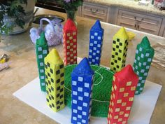 """This is a to scale replica of a Qudditch field cake. The cake its self is a """"green"""" velvet recipe with grassy green piped vanilla buttercream as the grass. The towers were constructed out of rice krispy treats covered and decorated with fondant with the respectable Hogwarts houses."""