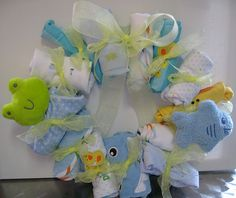 Baby gift wreath-Wreath frame wrapped with blue ribbon.  Wash clothes, caps, onesies, and toys rolled and tied on with yellow ribbon.