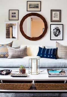 The final living room revealed: a gallery wall of black white and brown centers around a round wood framed mirror, the gray linen couch serves as the perfect base for bohemian batik and African indigo shibori throw pillows, and a low coffee table in front serves as both storage and the perfect display place. See more from our Honestly WTF Home Tour and Modern Living Room Makeover with The Studio at One Kings Lane: Inside Blogger Erica Chan Coffman's Oakland, CA Pad over on our Style Guide!