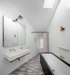 In this bathroom, white walls and ceilings make the brass accents and black cabinetry stand out. A skylight provides plenty of natural light to the space too.