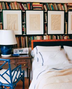 A colorful bookshelf serves as the perfect backdrop for this all-white bed. | http://domino.com