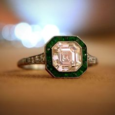 A lovely Diamond and Emerald Halo Engagement Ring, set in platinum and adorned with diamonds.