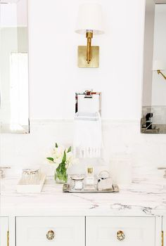 Bathroom with white walls, marble counter tops, white cabinets with brass details, and white and brass light fixture